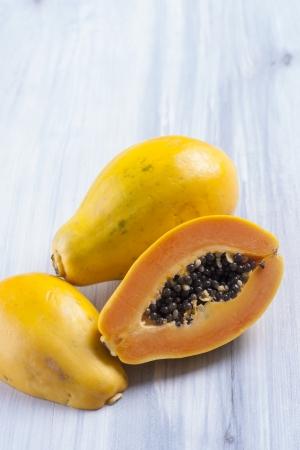 papaw: Close up photo of edible fruits - a papaya a solid  bright blue wooden table