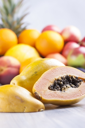 papaw: Close up photo of edible fruits - a papaya with other full colors fruits in the background on a solid  bright blue wooden table