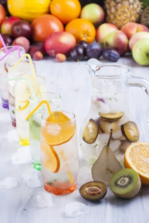jug: Fresh fruit and water drink with a sliced fruits - kiwi, pears, orange, plums, lemon, mint herb and ice cubes with some fruits in the background
