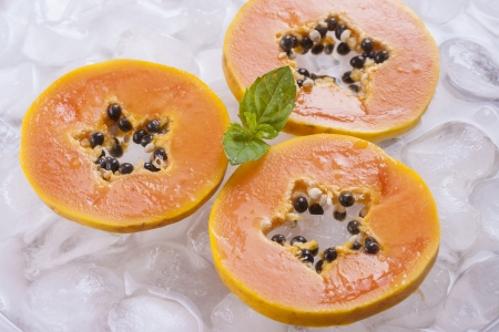 papaw: Composition of fresh orange papaya fruit slices with ice cubes and mint herb leaf.
