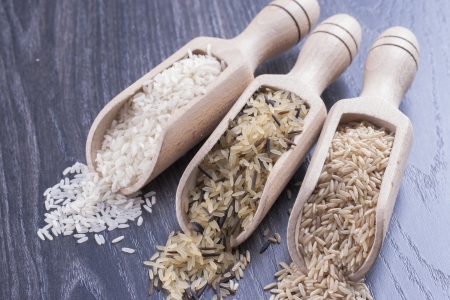 staple food: Close up photo of food ingredients - staple food - wooden spatula with a rice. Stock Photo