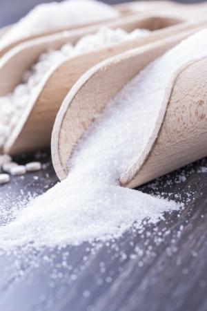 aspartame: Food ingredients - sugar, aspartame and salt on a dark solid wooden background.