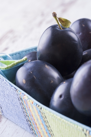 Fresh fruits - purple plums in a basket on a solid bright wooden background. photo