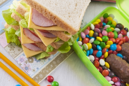 A concept which illustrate children health issues - an obesity - to big sandwich with some candies.