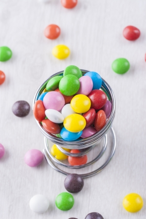 A close up photo of the junk food - a multicolor chocolate Smarties on a bright wooden background. Stock Photo