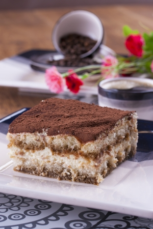 Close up photo of the tiramisu - sweet dessert with biscuits wiped in coffee with a mascarpone cheese and cocoa powder on the top on a white clay plate. photo