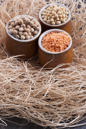 red gram: Close up photo of a raw food - orange seeds - red lentil, brown seeds - chickpeas, yellow beans - soybeans in a clay cup placed on a  wooden shavings. Stock Photo