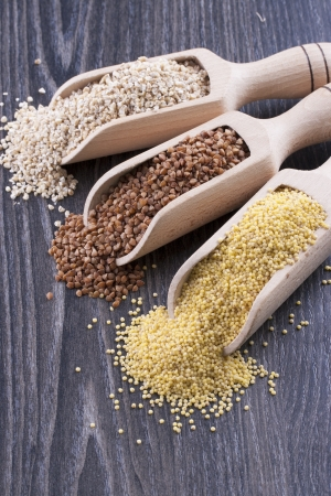 kasha: Close up photo of a eco raw food in the spoon - light brown pearl barley, dark brown kasha and yellow millet on a dark wooden background  Stock Photo