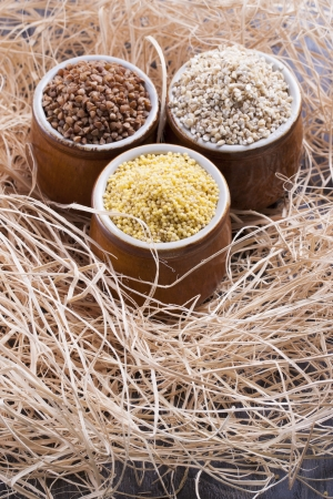 kasha: Close up photo of a eco raw food in the clay cup - light brown pearl barley, dark brown kasha and yellow millet on a  wooden shavings.