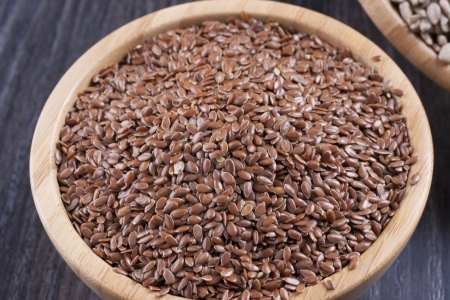 common flax: Close up photo of a raw eco food in the wooden bowl - dark brown linseeds placed on a dark wooden background.