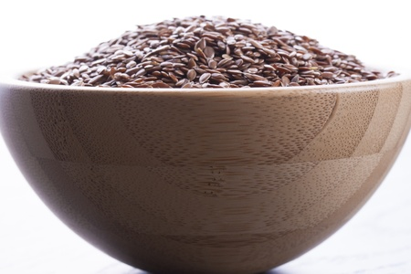 Close up photo of a raw eco food in the wooden bowl - dark brown linseeds placed on a dark wooden background. photo