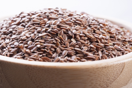 usitatissimum: Close up photo of a raw eco food in the wooden bowl - dark brown linseeds placed on a dark wooden background.