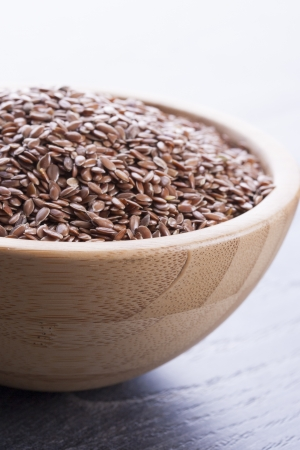 Close up photo of a raw eco food in the wooden bowl - dark brown linseeds placed on a dark wooden background.