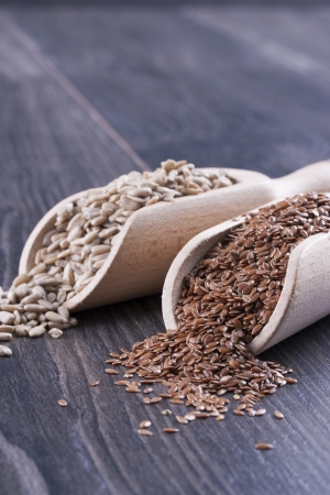 common flax: Close up photo of a raw eco food in the wooden spatula - light brown sunflower seeds and dark brown linseeds placed on a dark wooden background.
