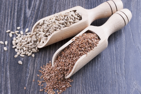 usitatissimum: Close up photo of a raw eco food in the wooden spatula - light brown sunflower seeds and dark brown linseeds placed on a dark wooden background.