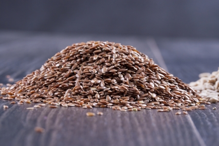 usitatissimum: Close up photo of a raw eco food - dark brown linseeds placed on a dark wooden background. Stock Photo