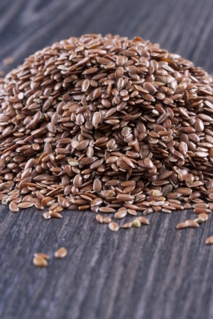 common flax: Close up photo of a raw eco food - dark brown linseeds placed on a dark wooden background. Stock Photo