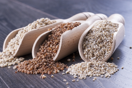 kasha: Close up photo of a raw eco food in the wooden spatula - light brown buckwheat groats, dark brown kasha and brown pearl barley placed on a dark wooden background.