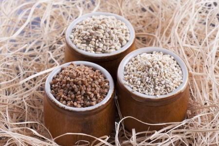 kasha: Close up photo of a raw eco food in the clay cup - light brown buckwheat groats, dark brown kasha and brown pearl barley placed on a dark wooden background.