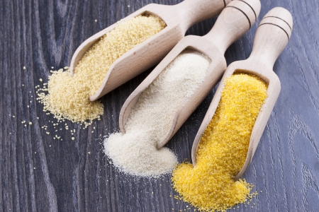 farina: Close up photo of a raw eco food in the wooden spatulas - light yellow couscous, light brown farina and dark yellow cornmeal placed on a dark wooden background. Stock Photo