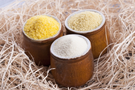 Close up photo of a raw eco food in the clay cup - light yellow couscous, light brown farina and dark yellow cornmeal placed on a dark wooden background.