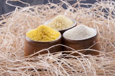 farina: Close up photo of a raw eco food in the clay cup - light yellow couscous, light brown farina and dark yellow cornmeal placed on a dark wooden background.