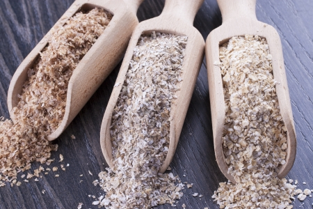 Close up photo of a cereal grain product in a wooden scoop - dark brown wheat bran, light brown secale bran, and mid-brown arena bran placed on a dark wooden background. Stock Photo - 22214035