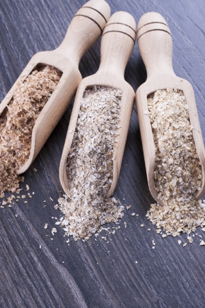 Close up photo of a cereal grain product in a wooden scoop - dark brown wheat bran, light brown secale bran, and mid-brown arena bran placed on a dark wooden background. Stock Photo - 22214038