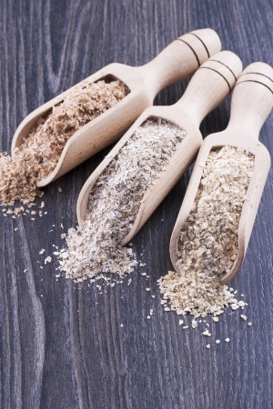 secale: Close up photo of a cereal grain product in a wooden scoop - dark brown wheat bran, light brown secale bran, and mid-brown arena bran placed on a dark wooden background. Stock Photo