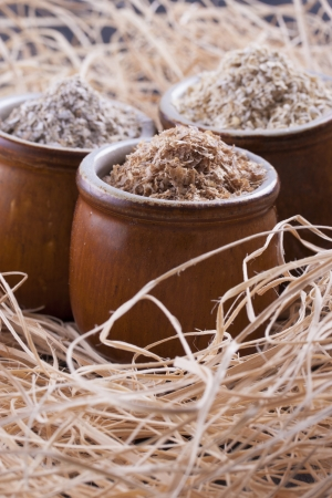 Close up photo of a cereal grain product in a clay cup - dark brown wheat bran, light brown secale bran, and mid-brown avena bran placed on a wooden shavings. Stock Photo - 22214055