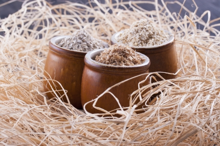 secale: Close up photo of a cereal grain product in a clay cup - dark brown wheat bran, light brown secale bran, and mid-brown avena bran placed on a wooden shavings.