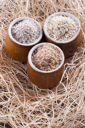 Close up photo of a cereal grain product in a clay cup - dark brown wheat bran, light brown secale bran, and mid-brown avena bran placed on a wooden shavings. Stock Photo - 22214059