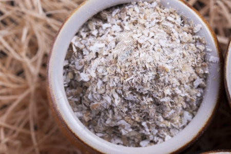 Close up photo of a cereal grain product in a clay cup - light brown secale bran placed on a wooden shavings. Stock Photo - 22214063