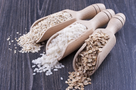 Close up photo of a breakfast cereal in a wooden scoop - light brown barley flakes, white rice flakes and dark brown secale flakes placed on a dark wooden background. Stock Photo - 22214069