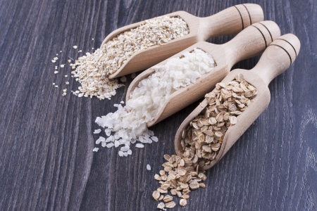 secale: Close up photo of a breakfast cereal in a wooden scoop - light brown barley flakes, white rice flakes and dark brown secale flakes placed on a dark wooden background. Stock Photo