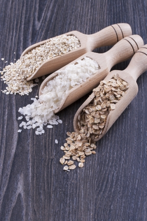 Close up photo of a breakfast cereal in a wooden scoop - light brown barley flakes, white rice flakes and dark brown secale flakes placed on a dark wooden background. Stock Photo - 22214074