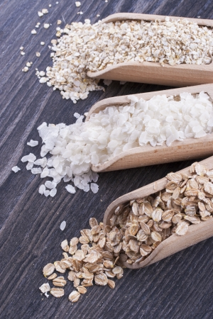 Close up photo of a breakfast cereal in a wooden scoop - light brown barley flakes, white rice flakes and dark brown secale flakes placed on a dark wooden background. Stock Photo - 22214080