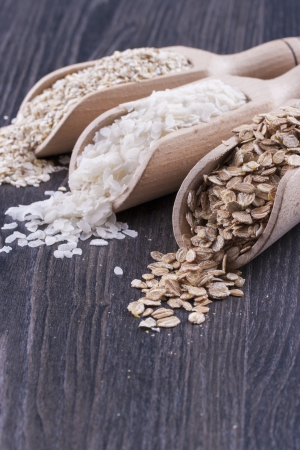 Close up photo of a breakfast cereal in a wooden scoop - light brown barley flakes, white rice flakes and dark brown secale flakes placed on a dark wooden background. Stock Photo - 22214083