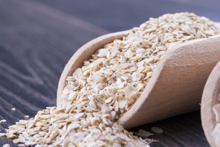 secale: Close up photo of a breakfast cereal in a wooden scoop - light brown barley flakes placed on a dark wooden background.