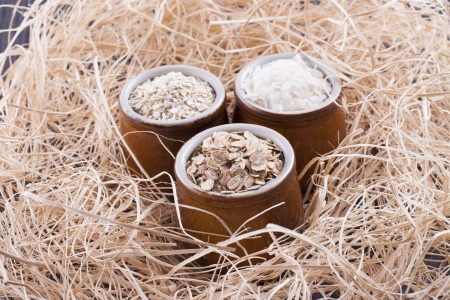 Close up photo of a cereal grain product in a clay cup - light brown barley flakes, white rice flakes and dark brown secale flakes placed on a wooden shavings. Stock Photo - 22214096