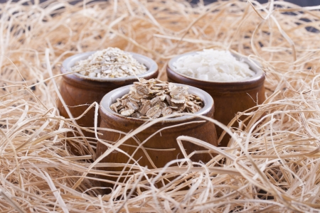 Close up photo of a cereal grain product in a clay cup - light brown barley flakes, white rice flakes and dark brown secale flakes placed on a wooden shavings. Stock Photo - 22214098