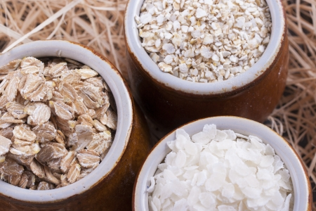 secale: Close up photo of a cereal grain product in a clay cup - light brown barley flakes, white rice flakes and dark brown secale flakes placed on a wooden shavings.