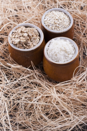 Close up photo of a cereal grain product in a clay cup - light brown barley flakes, white rice flakes and dark brown secale flakes placed on a wooden shavings. Stock Photo - 22214104