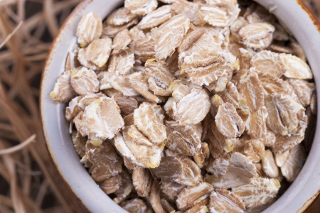 Close up photo of a cereal grain product in a clay cup - dark brown secale flakes placed on a wooden shavings. Stock Photo - 22214111