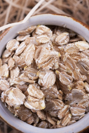 secale: Close up photo of a cereal grain product in a clay cup - dark brown secale flakes placed on a wooden shavings.