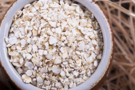 Close up photo of a cereal grain product in a clay cup - light brown barley flakes placed on a wooden shavings. Stock Photo - 22214113