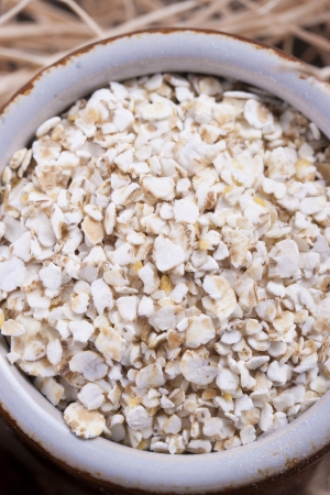Close up photo of a cereal grain product in a clay cup - light brown barley flakes placed on a wooden shavings. Stock Photo - 22214115