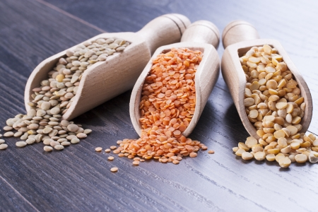 Close up photo of a healthy seeds in a wooden scoop - light brown colored green lentils, orange colored red lentils and yellow pea placed on a dark wooden background.