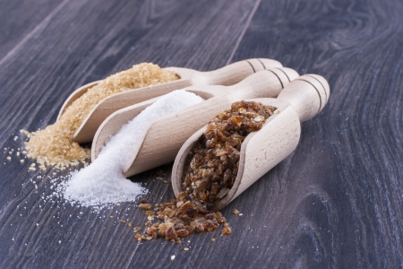 Close up photo of a food ingredients in a wooden scoop - brown sugar cane, white sugar and large pieces of crystalized sugar placed on a dark wooden background. photo