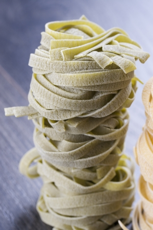 Close up photo of a noodles - fettuccine placed on a dark wooden background. photo